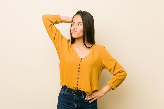 Jeune femme hispanique contre un mur beige touchant l'arrière de la tête, réfléchissant et faisant un choix.