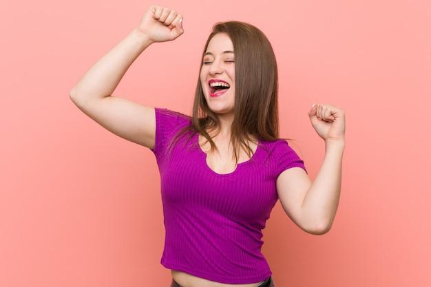 Jeune femme hispanique contre un mur rose célébrant une journée spéciale, saute et lève les bras avec énergie.