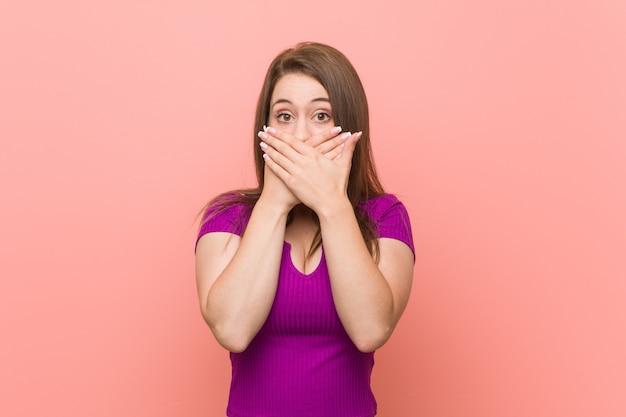Jeune femme hispanique contre un mur rose choqué couvrant la bouche avec les mains.