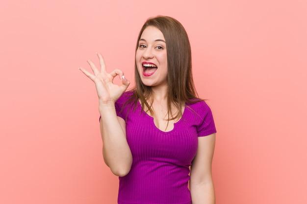 Jeune femme hispanique contre un mur rose cligne de l'oeil et tient un geste correct avec la main.