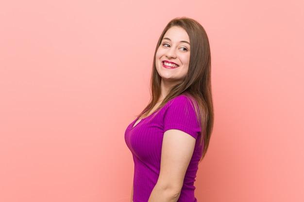 Une jeune femme hispanique contre un mur rose semble souriante, enjouée et agréable.