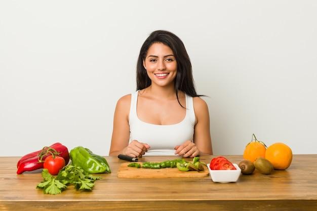 Jeune femme hispanique, couper des légumes sur la table
