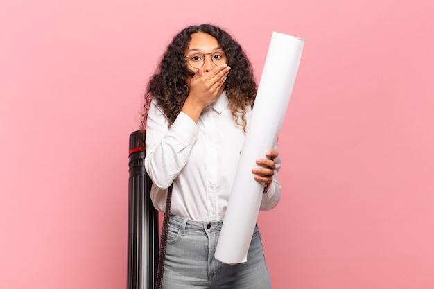 Jeune femme hispanique couvrant la bouche avec les mains avec une expression choquée et surprise, gardant un secret ou disant oups. concept d'architecte