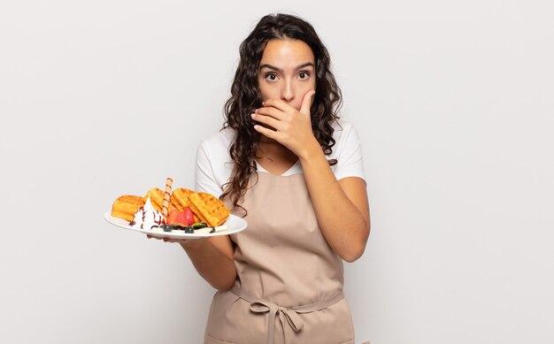 Jeune femme hispanique couvrant la bouche avec les mains avec une expression choquée et surprise, en gardant un secret ou en disant oups