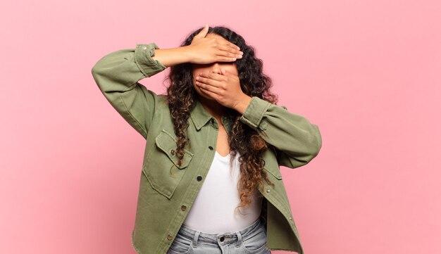 Jeune femme hispanique couvrant le visage avec les deux mains disant non à la caméra ! refuser des photos ou interdire des photos