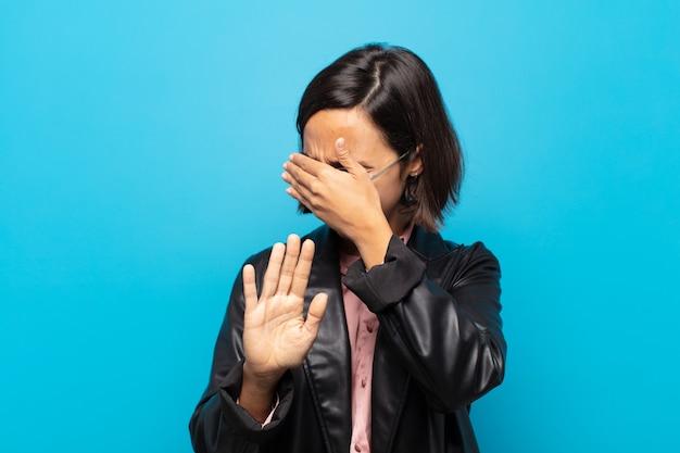 Jeune femme hispanique couvrant le visage avec la main et mettant l'autre main devant pour arrêter l'appareil photo, refusant des photos ou des images