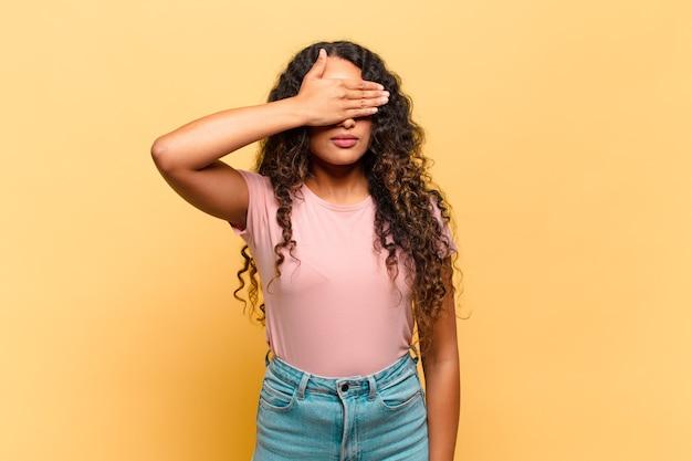 Jeune femme hispanique couvrant les yeux d'une main se sentant effrayée ou anxieuse, se demandant ou attendant aveuglément une surprise