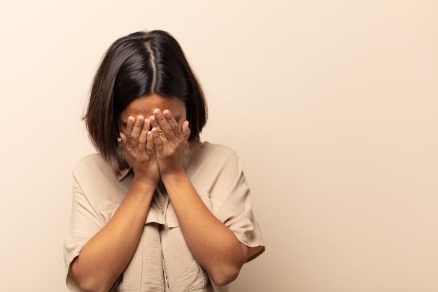 Jeune femme hispanique couvrant les yeux avec les mains avec un regard triste et frustré de désespoir, de pleurs, de vue latérale