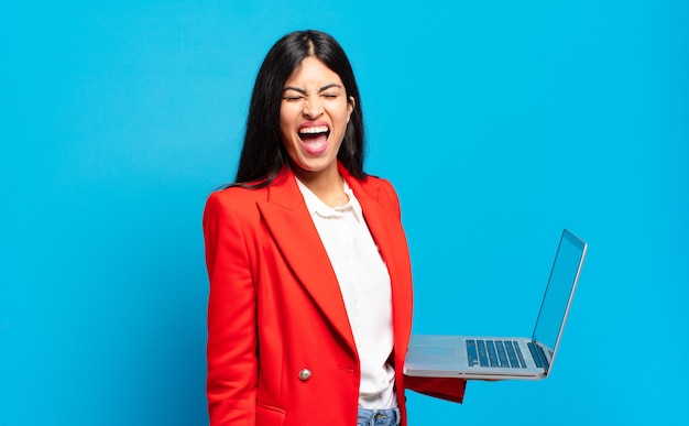 Jeune femme hispanique criant agressivement, l'air très en colère, frustré, indigné ou agacé, criant non. concept d'ordinateur portable