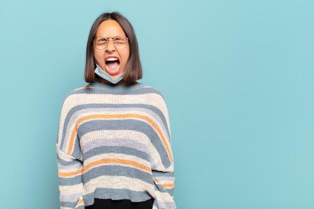 Jeune femme hispanique criant agressivement, ayant l'air très en colère, frustrée, indignée ou agacée, criant non