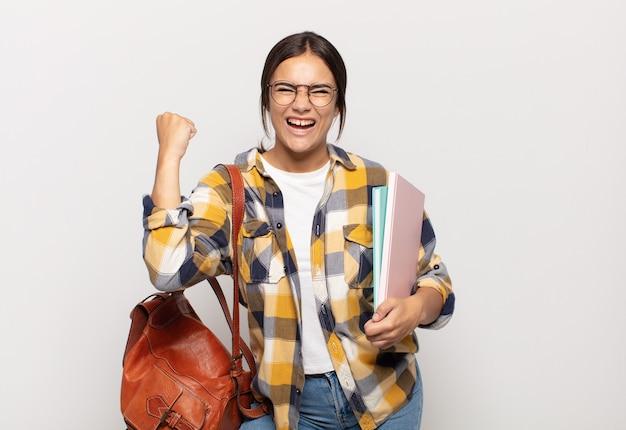 Jeune femme hispanique criant agressivement avec une expression de colère ou avec les poings serrés célébrant le succès
