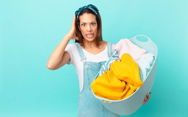 Jeune femme hispanique criant avec les mains en l'air et lavant les vêtements