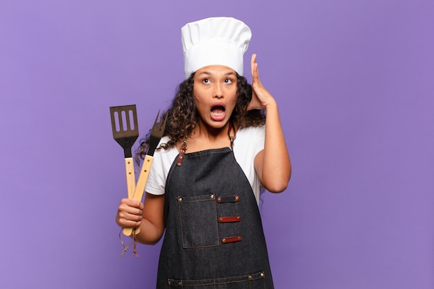 Jeune femme hispanique criant avec les mains en l'air, se sentant furieuse, frustrée, stressée et bouleversée. concept de chef de barbecue