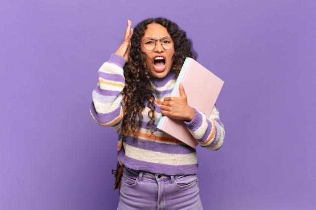 Jeune femme hispanique criant avec les mains en l'air, se sentant furieuse, frustrée, stressée et bouleversée. concept d'étudiant