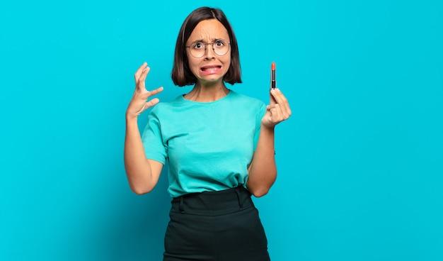 Jeune femme hispanique criant avec les mains en l'air