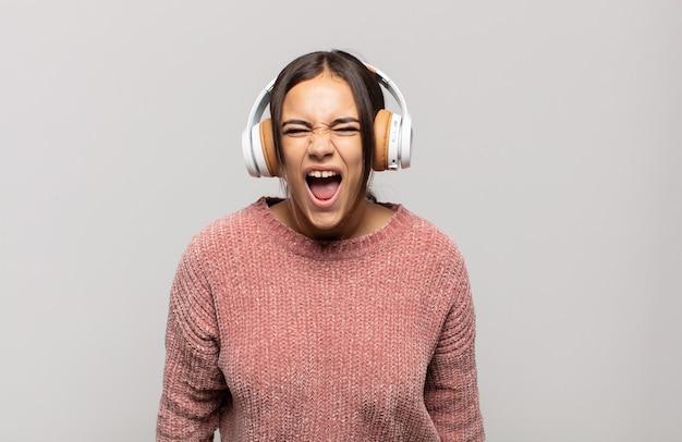 Jeune femme hispanique criant de manière agressive, à la très en colère, frustré, indigné ou agacé, crier non