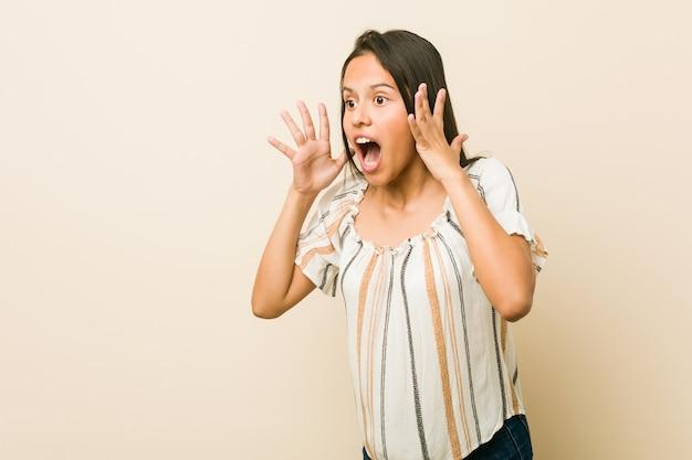 Une jeune femme hispanique crie fort, garde les yeux ouverts et les mains tendues.