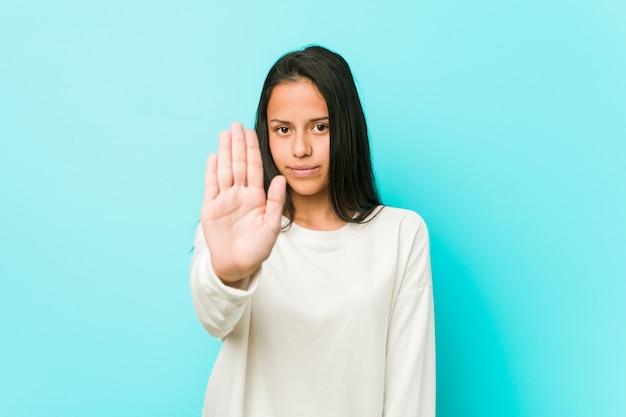 Jeune femme hispanique debout avec la main tendue montrant le panneau d'arrêt, vous empêchant.