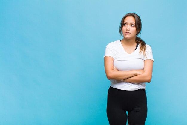 Jeune femme hispanique doutant ou pensant, se mordant la lèvre et se sentant insécurité et nerveuse, à la recherche de copier l'espace sur le côté
