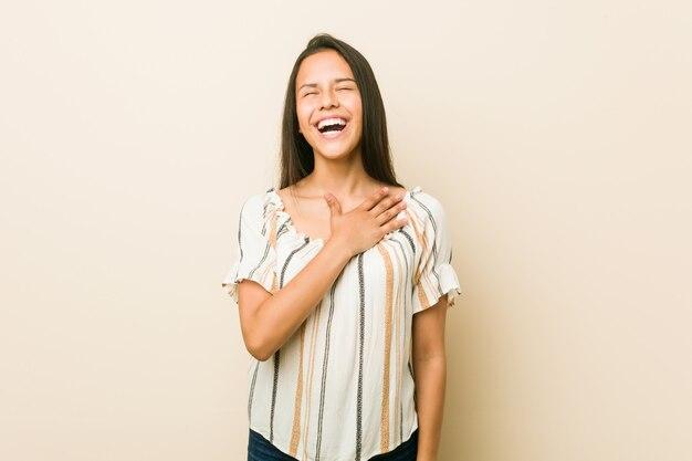 Jeune femme hispanique éclate de rire en gardant la main sur la poitrine.