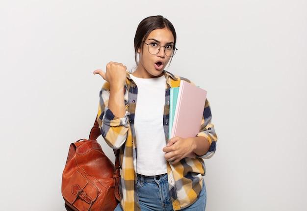 Jeune femme hispanique à étonné d'incrédulité, pointant sur l'objet sur le côté et disant wow, incroyable