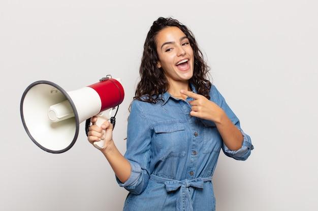 Jeune femme hispanique à excité et surpris en pointant vers le côté et vers le haut pour copier l'espace