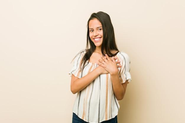 Jeune femme hispanique a une expression amicale, appuyant de la paume contre la poitrine. concept de l'amour