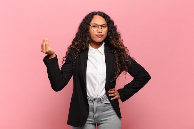 Jeune femme hispanique faisant capice ou geste d'argent, vous disant de payer vos dettes!. concept d'entreprise