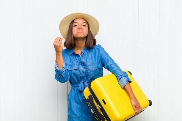 Jeune femme hispanique faisant capice ou geste d'argent