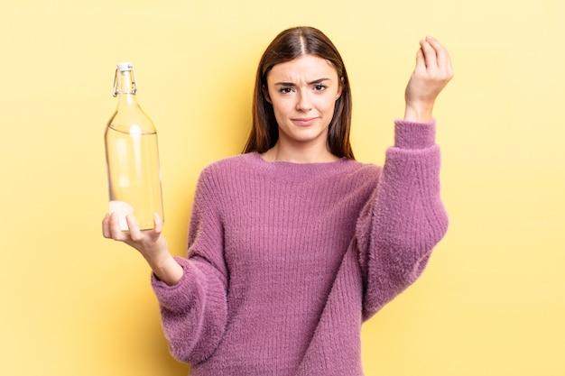 Jeune femme hispanique faisant un geste de capice ou d'argent, vous disant de payer. concept de bouteille d'eau