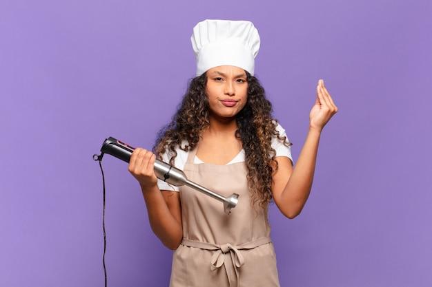 Jeune femme hispanique faisant un geste de capice ou d'argent, vous disant de payer vos dettes !. concept de chef