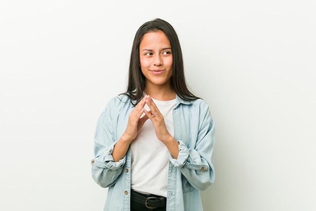 Jeune femme hispanique faisant un plan à l'esprit, mettant en place une idée.