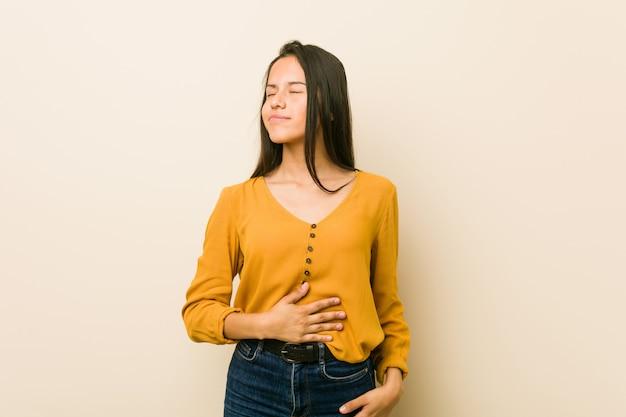 Jeune femme hispanique sur un fond beige touche le ventre, sourit doucement, concept de restauration et de satisfaction.