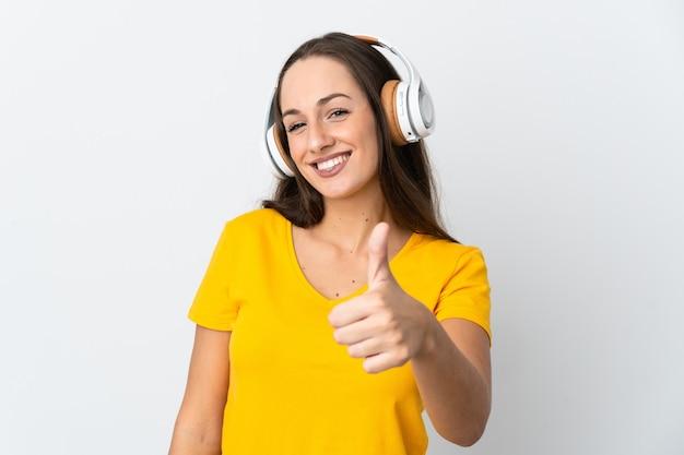 Jeune femme hispanique sur fond blanc isolé à l'écoute de la musique et avec le pouce vers le haut