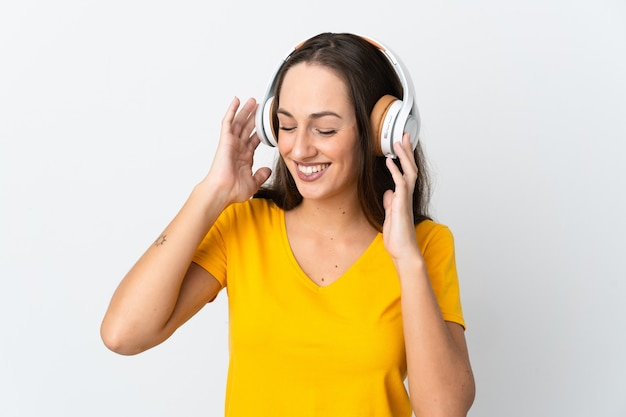 Jeune femme hispanique sur fond blanc isolé, écouter de la musique