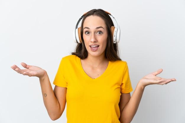 Jeune femme hispanique sur fond blanc isolé surpris et écouter de la musique