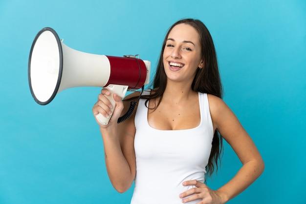 Jeune femme hispanique sur fond bleu isolé tenant un mégaphone et souriant