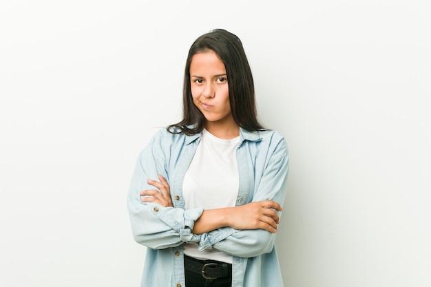 Jeune femme hispanique, fronçant le visage avec mécontentement, garde les bras croisés.
