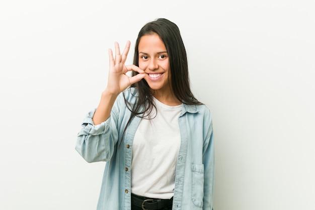 Jeune femme hispanique gaie et confiante montrant le geste ok.