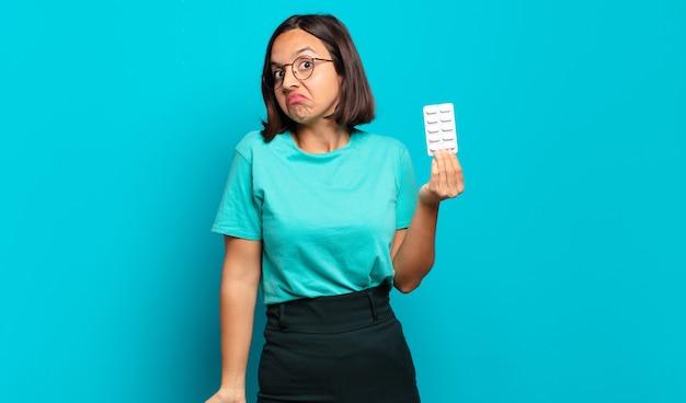 Jeune femme hispanique haussant les épaules, se sentant confus et incertain, doutant des bras croisés et regard perplexe
