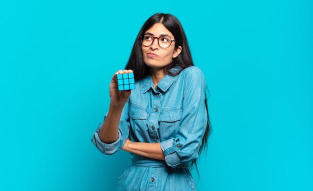 Jeune femme hispanique haussant les épaules, se sentant confuse et incertaine, doutant les bras croisés et le regard perplexe. concept de problème de renseignement