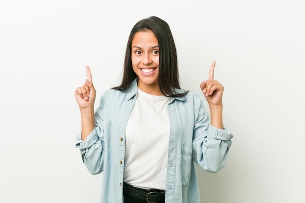 Jeune femme hispanique indique avec les deux doigts avant un espace vide.