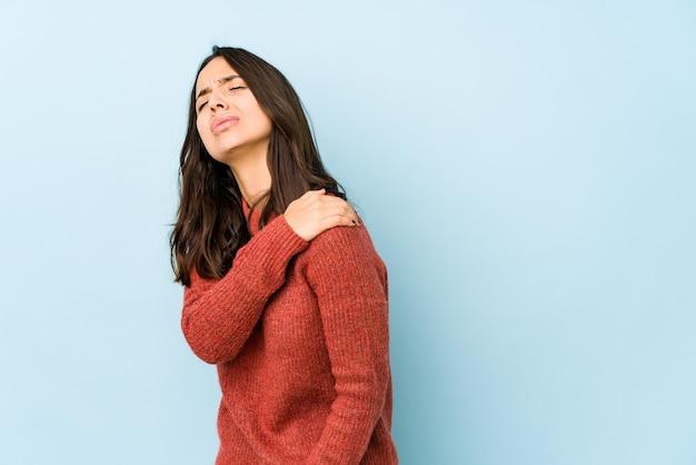 Jeune femme hispanique isolée ayant une douleur à l'épaule