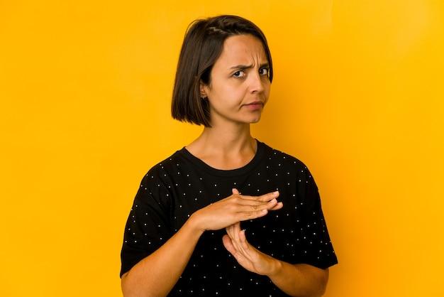 Jeune femme hispanique isolée sur jaune montrant un geste de temporisation.