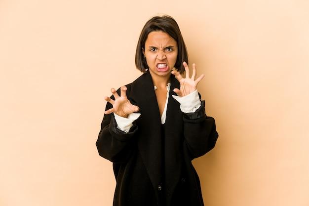 Jeune femme hispanique isolée montrant des griffes imitant un chat, geste agressif.
