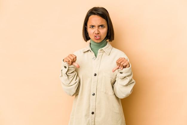 Jeune femme hispanique isolée montrant le pouce vers le bas et exprimant l'aversion.