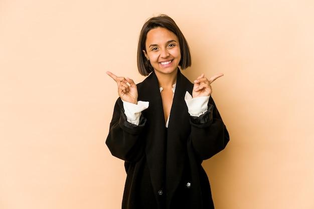 Jeune femme hispanique isolée pointant vers différents espaces de copie, en choisissant l'un d'entre eux, montrant avec le doigt.