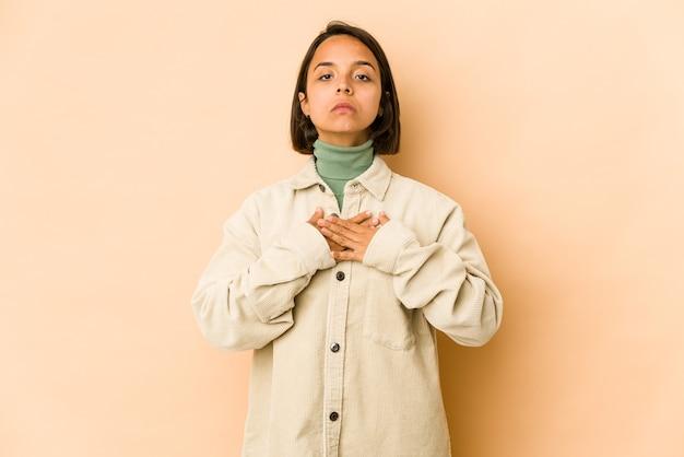 Jeune femme hispanique isolée prêtant serment, mettant la main sur la poitrine.