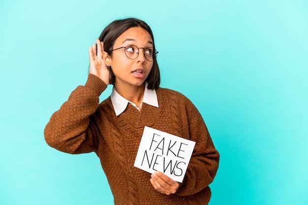 Jeune femme hispanique isolée tenant une fausse affiche de nouvelles