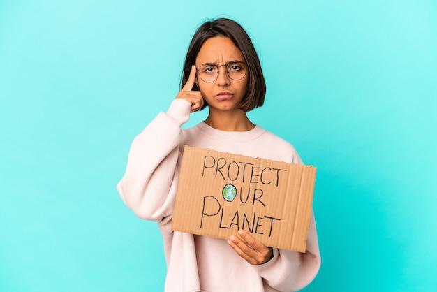 Jeune femme hispanique isolée tenant une pancarte protéger notre planète
